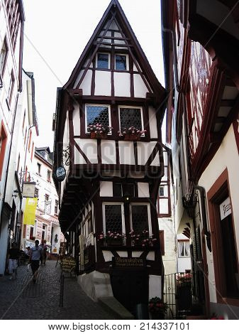 Bernkastel Germany - 1 July 2010: People are walking around the traditional old wooden house on street in Germany