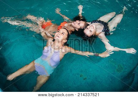 Funny female teenagers fooling around in the swimming pool laughing and enjoying their weekends.