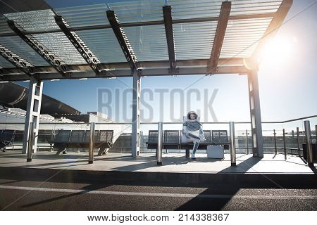 Full length portrait of cheerful male astronaut sitting on bench near grey suitcase. He is waiting for flight at space station. Copy space