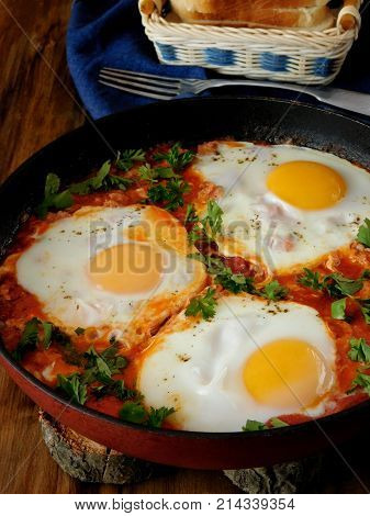 A pan of fried eggs with tomato sauce and parsley on a wooden background. Shakshuka a traditional meal of the Jewish cuisine