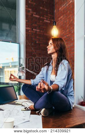 Side view of pretty creative female freelancer sitting in lotus pose on working desk under light bulb waiting for idea to come.