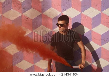 Youngster in black sunglasses and casual clothing holding bomb with colored red smoke at street.