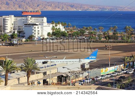 Eilat, Israel - MAY 24: plane of israeli airline Arkia, landed at the airport of Eilat on the background of luxurious hotels, Israel, on May 24, 2017 in  Eilat, Israel