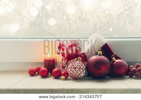 Christmas styled scene with glowing candle and christmas decorations on winter windowsill, retro toned