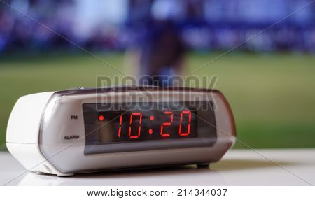 White electronic clock with a red dial. White clock with an alarm clock.