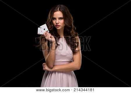 Attractive young woman in a sexy light dress holding the winning combination of poker cards. Two Aces. Studio shot on a black background. Casino