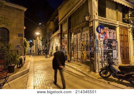 ATHENS GREECE - NOVEMBER 3 2017: building corner in Psyri district of Athens' city center left to decay and ruin with people walking in the dark
