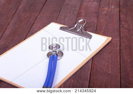 Closeup of a medical stethoscope with folder on wooden background, selective focus.