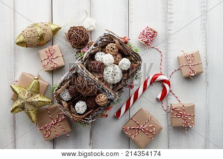 Christmas rattan balls in basket presents and gift boxes wrapped in kraft paper on white wooden background copy space