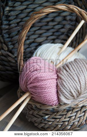 Yarn balls with knitting needles in the basket on the wooden background. Toned.