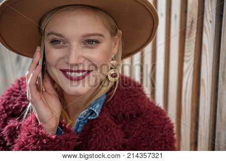 Friendly call. Portrait of excited young woman enjoying communication by cellphone. She is smiling near wooden fence on background