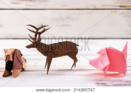 Animal figurines on wooden background. Finished lion, deer, pig origami models for school exhibition. Arts and crafts.
