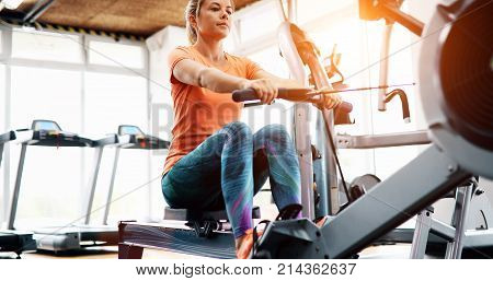 Young blonde woman working on rowing machine in gym