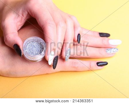 Black, white Nail art manicure. Holiday style bright Manicure with sparkles. Bottle of Nail Polish. Beauty hands. Stylish Nails, Nail Polish.