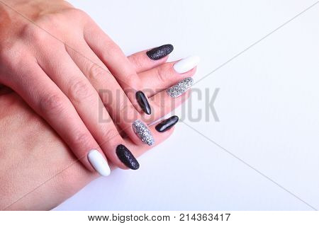 Black, white Nail art manicure. Holiday style bright Manicure with sparkles. Beauty hands. Stylish Nails, Nail Polish.