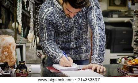 Handsome male shopkeeper keeping accountancy books in his store, writing on paper sheets and reading records