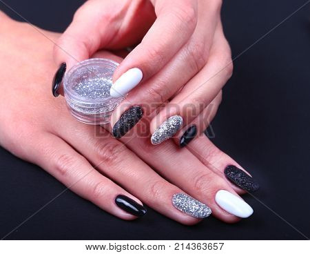 Black, white Nail art manicure. Holiday style bright Manicure with sparkles. Bottle of Nail Polish. Beauty hands. Stylish Nails, Nail Polish.