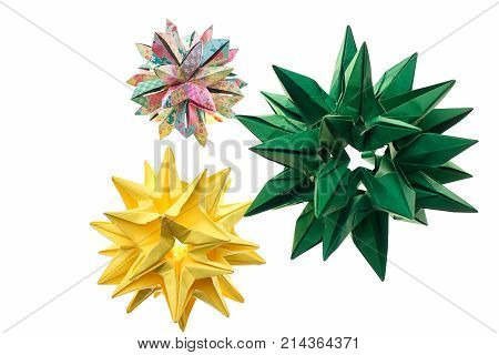 Three spiky origami decorations on white. Stars and cosmic bodies. Advanced level of paper folding art.