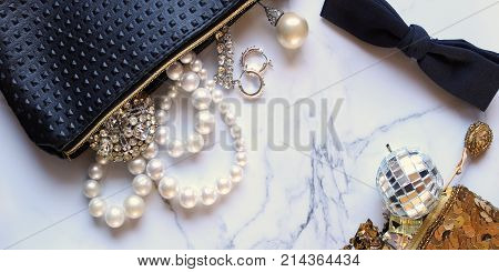 Elegant luxury jewelry accessories spill onto white marble copy space.