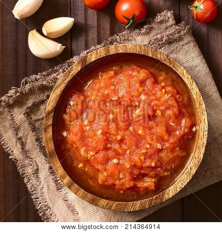 Homemade traditional Italian marinara or pomodoro tomato sauce made of fresh tomato garlic dried oregano and salt served in wooden bowl with ingredients on the side photographed overhead on dark wood with natural light (Selective Focus Focus on the top of