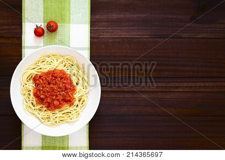 Traditional Italian Spaghetti alla Marinara (spaghetti with tomato sauce) in bowl photographed overhead on dark wood with natural light