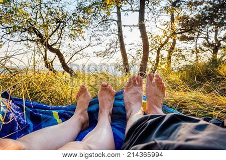 Closeup of female and male feet lying on blanket at sunset. Romance in forest meadow.