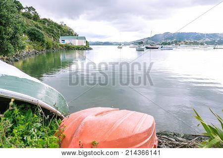 Orange clinker rowing dinghy with boats moored in Whangaroa Harbour Far North District Northland New Zealand NZ in background
