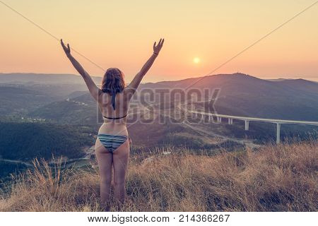 Attractive brunette performing yoga form at sunset. Greeting the sun.
