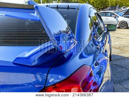 Blue Car With Reflective Paint In Parking Lot