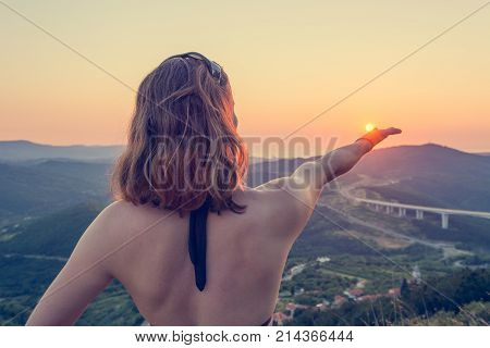 Attractive brunette holding a sun in her hand. Marin sunset concept.