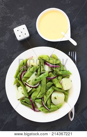 Green bean potato and red onion salad with parsley hollandaise sauce on the side photographed overhead on slate with natural light