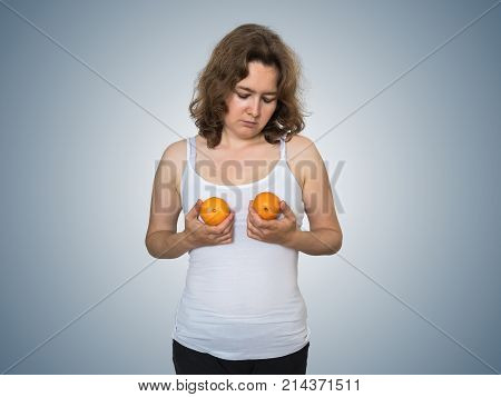 Young sad and unsatisfied woman is holding two tangerines in hands above her breast. Plastic surgery and silicone implants concept.