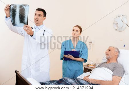 The old man lies on a cot in the medical ward. Next to him is a doctor and a nurse. The doctor looks at the X-ray of the old man. The nurse and the old man also examine the picture.