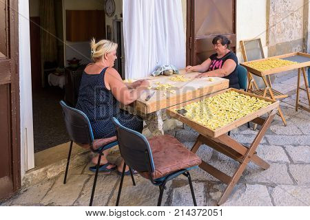 Bari Italy - September 2 2016: Women maki traditional italian pasta called orecchiette on the street of old town of Bari