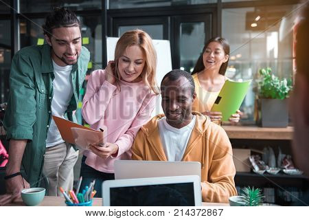 African young man is sitting at table and showing screen of laptop to his colleagues while sharing his idea with them. They are expressing gladness while looking at monitor. Asian woman in background