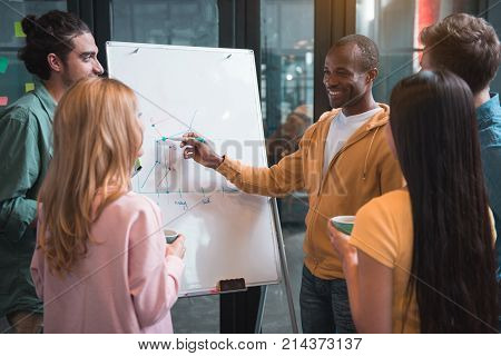Involved in discussion. Positive multinational business team members are standing around flipchart and looking at board with graphics. African man is holding marker and pointing on panel with smile