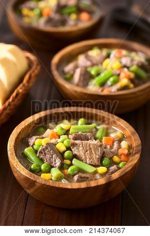Beef stew or soup with colorful summer vegetables (pea carrot sweet corn green bean onion) in wooden bowls with bread slices on the side photographed on dark wood with natural light (Selective Focus Focus in the middle of the first dish)