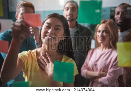 Exciting task. Optimistic asian girl is working with color stickers and showing interest while standing behind transparent wall. Her multinational team is standing in background. Selective focus