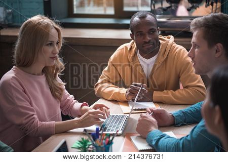 Smiling girl looking at serene man while typing in laptop. Serious mulatto comrade listening them and making notes. Profession concept