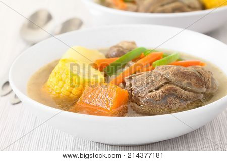 Traditional Chilean Cazuela de Vacuno or Cazuela de Carne a beef soup with potato corn pumpkin carrot bell pepper onion and rice photographed with natural light (Selective Focus Focus on the front of the meat and the pumpkin)