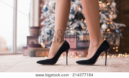 Pretty legs in beautiful high heel shoes with a Christmas gifts and New Year's Tree. New Year's party 2018. Christmas Eve.