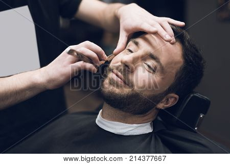 The barber shaves his head, mustache and beard to the man in the barbershop. The stylist uses a classic sharp razor, neatly shaving the client.