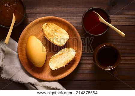 Toasted bread rolls on wooden plate with strawberry and peach jam in rustic bowls and tea on the side photographed overhead on dark wood with natural light