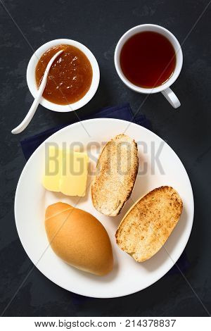 Toasted bread rolls with butter peach jam and tea on the side photographed overhead on slate with natural light