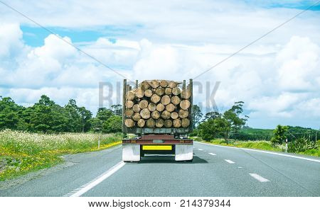 Logging industry truck driving on State Highway One road in Northland North Island New Zealand NZ