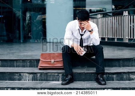 Unemployed Tired or stressed businessman sitting on the walkway after work Stressed businessman concept poster