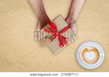 Close Up Hand Woman Holding Gift Box On Brown Paper With Coffee Cup.