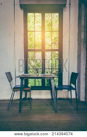 Dining room interior. Loft-style window with nature view cement walls and wooden floor. Two table sets and flower vase on table. Image contain certain grain or noise. Vintage film filter effect.