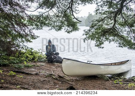 Rainy day in Canada Ontario Lake two rivers white blank Canoe Canoes parked on island in Algonquin National Park