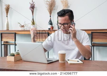 asia casual man arm up celebrate good new from mobile at laptop in coffee shopsuccess business conceptwork outside officework at home